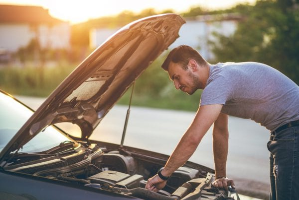 person checking car oil